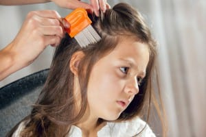 Mother treating daughter's hair against lice. Selective focus